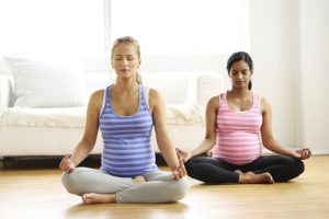 Two pregnant women practicing yoga
